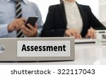 Small photo of assessment file on desk with executives and auditors in office.