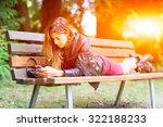 girl lying on a bench using... | Shutterstock . vector #322188233