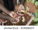 black baby hands under african... | Shutterstock . vector #323006027