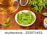 Small photo of Lemon verbena leaves on white bowl and verbena tea on wooden table. Aloysia citrodora.