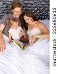 loving family reading a story... | Shutterstock . vector #323680613