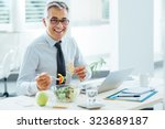 smiling businessman sitting at... | Shutterstock . vector #323689187