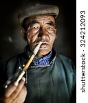 Small photo of Mongolian Traditional Dress Smoking Pipe Solitude Concept