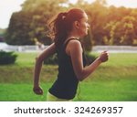 pretty sporty woman jogging at... | Shutterstock . vector #324269357