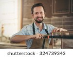 portrait of a craftsman using a ... | Shutterstock . vector #324739343
