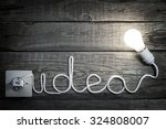 Small photo of Creativity concept idea letters with bulb and wire abstract background