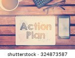 Small photo of Notebook with text inside Action Plan on table with coffee, mobile phone and glasses.