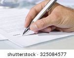 close up shot of hand signing a ... | Shutterstock . vector #325084577