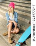 Small photo of Active way of life. Agreeable vivacious charming delighted young lady sitting on the footsteps near her skateboard while resting