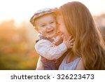 mother son in a pumpkin patch | Shutterstock . vector #326223473