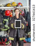 Small photo of Portrait of confident firewoman showing digital tablet with blank screen at fire station