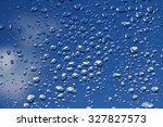rain drops on window with blue...