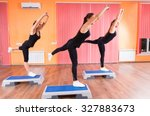 Small photo of Three Fit Girls Doing Balance Exercise with One Leg on Top of Aerobic Step Platforms Inside the Gym.