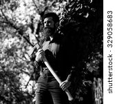 Small photo of One handsome strong stylish male logger of young man with long lush beard and moustache in shirt holding wooden axe standing near tree outdoor on natural background black and white, square