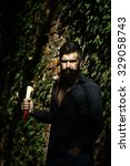 Small photo of One handsome strong stylish male logger of young man with long lush black beard and moustache in shirt holding wooden axe standing near brick wall outdoor, vertical picture
