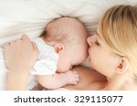 Young Mother Breastfeeds Her...