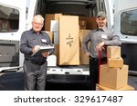 Small photo of Group of delivery men with parcels near shipping truck. Parcel service.