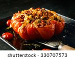 Small photo of Appetizing stuffed oven roasted ripe tomato with a spicy savory stuffing being displayed on a spatula for healthy starters or accompaniment to dinner