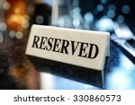 Small photo of Restaurant reserved table sign with places setting and wine glasses ready for a party