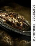 Small photo of Creatively lit image of broken pieces of rocky road chocolate on an antique pewter serving plate against a dark, rustic background. Accommodation for copy space.