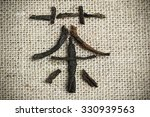 Small photo of Chinese logogram Tea made of tea leaves on flax background close up