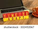 Small photo of Time To Adapt written on a wooden cube in front of a laptop