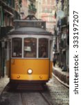 Small photo of Travel blurred backgrounds - yellow tram with people in Lisbon, Portugal. Trams are the symbol of the city, operating since 1873