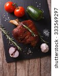 Small photo of Baked pork shank and fresh vegetables on a slate board on the table. vertical top view