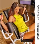 Small photo of Girl workout on multistation bodybuilding in sport gym.