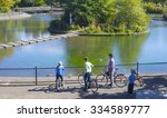 a young family observe ducks at ... | Shutterstock . vector #334589777