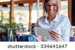 smiling woman using tablet in a ... | Shutterstock . vector #334641647