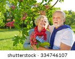 Small photo of Senior couple in spring under a blooming chestnut tree (Aesculus x carnea)