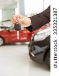 saleswoman holding a car key at ... | Shutterstock . vector #335321387
