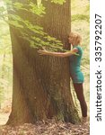 young woman hugging the tree in ... | Shutterstock . vector #335792207