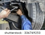 Small photo of Hands mechanics to repair the suspension on the car