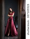 Small photo of Attractive woman in long claret lace dress. Reflected in mirror