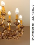 Small photo of Detail of chandelier alight, golden
