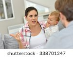 Small photo of Man and woman arguing in front of baby
