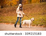 Stock photo portrait of a beautiful young woman with her dog while walking in the autumn park 339215183