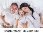happy family lying on a bed... | Shutterstock . vector #339305633