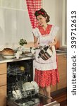 Small photo of Housewife loads the dishes in the dishwasher. 1950s style post processing emulation.