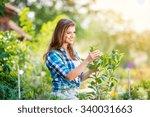 Beautiful Young Woman Gardenin...
