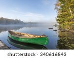 Green Canoe Tied To Dock On A...