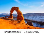 delicate arch on sunset in snow ...
