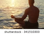 Small photo of Close up on man meditating in yoga position on the beach near the sea at sunset