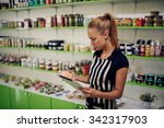 Small photo of Young beautiful female consultant checks the quality of spa goods verifying information on digital tablet, woman owner using touch pad for work while standing in cosmetics store or pharmacy interior