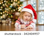 Little Girl In Santa Hat Write...