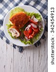 Small photo of Chicken schnitzel cordon bleu and a salad on a plate on a table. vertical top view
