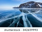 Lake Baikal in winter day. Cracks on the smooth surface of the ice near the cliffs of Olkhon Island