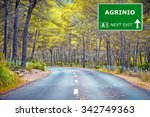 Small photo of AGRINIO road sign against clear blue sky